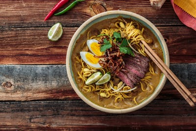 Boiled noodles, beef steak, egg, onion in a bowl, asian cuisine, copy space