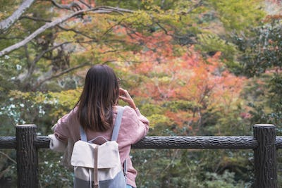 Lonely woman standing absent minded and looking at leaves change color in autumn