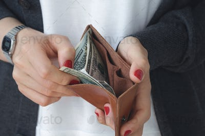 The girl pays in the shop. Hands holding an open leather orange slim purse with cash dollars.
