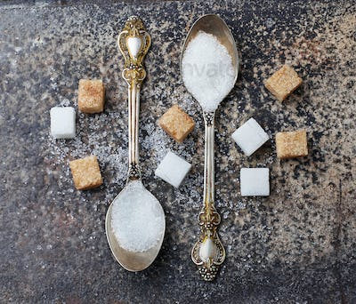 White and brown sugar in spoon.
