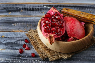 Ripe dissected pomegranate in wooden bowl