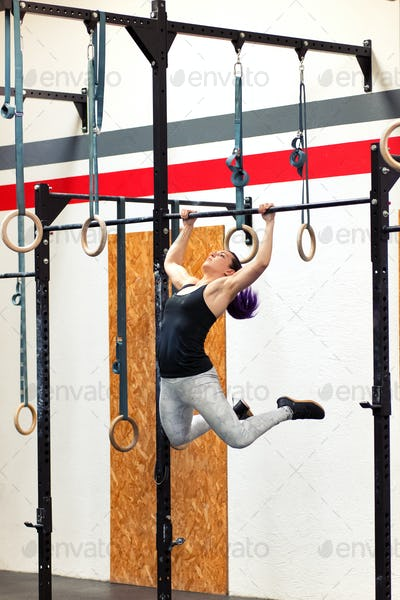 Fit young woman doing pull-ups on rings