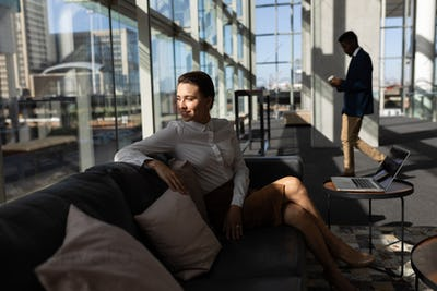 Businesswoman sitting on the sofa and looking away in modern office