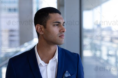 Front view of thoughtful young mixed-race businessman looking away standing in modern office