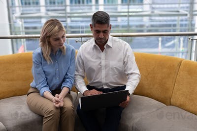 Front view of Caucasians business executives using laptop sitting on the sofa in modern office