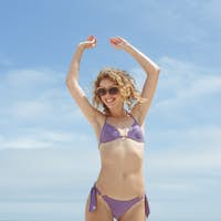 Front view of caucasian woman standing with hand stretched at beach on sunny day