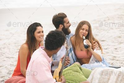 Man playing guitar while friends enjoying on beach