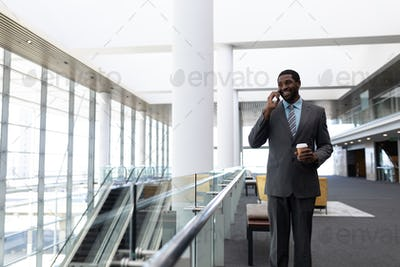 Businessman with coffee cup talking on mobile phone standing in modern office