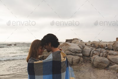 Side view of young Caucasian couple wrapped in blanket kissing each other standing at beach
