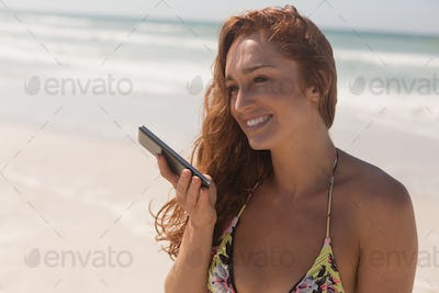 Happy beautiful young woman in bikini talking to her mobile phone at beach. She is smiling