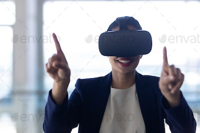 Businesswoman using virtual reality headset standing in modern office