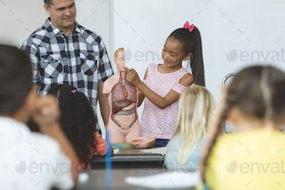 Schoolgirl standing behind professor desk in classroom at school