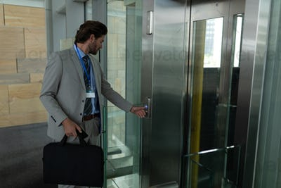 Side view of smart young Caucasian businessman waiting for the elevator in modern office