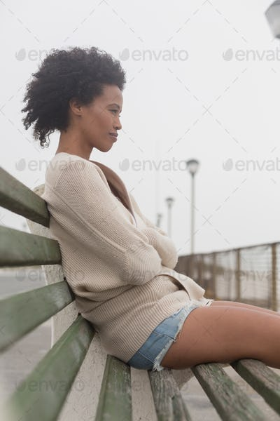 Side view of thoughtful young African American woman with arms crossed sitting on bench at promenade