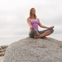 Low angle view of caucasian blonde woman perform yoga on the beach. She is relaxed
