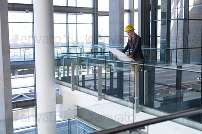 Side view of young blonde Caucasian female architect looking at blueprint in modern office