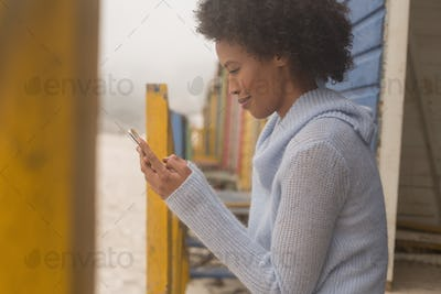 Side view of happy young African American woman using her mobile phone at beach hut. She is smiling