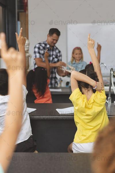 Schoolkids raising hand at school