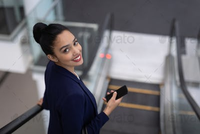 Businesswoman with mobile phone looking at camera on escalator in modern office