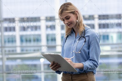 Front view of beautiful young blonde Caucasian female doctor writing on clipboard standing in clinic