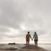 Rear view of young Caucasian couple standing hand in hand on rock near beach