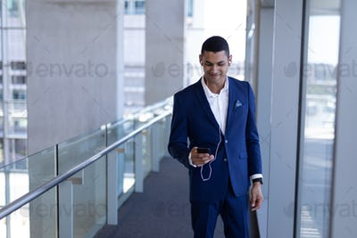Businessman listening music on mobile phone standing in modern office