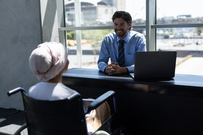 Young female executive interacting with handsome young Caucasian businessman at desk in office