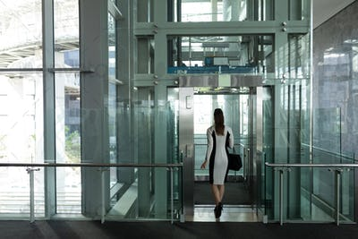 Rear view of beautiful Caucasian female executive getting in modern elevator at office