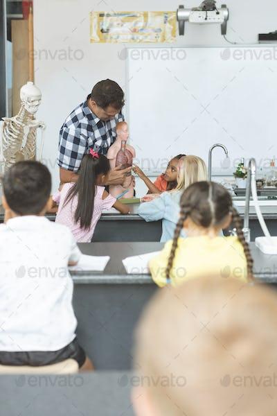 Teacher holding a dummy skeleton in classroom