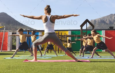 Trainer teaching yoga to students on yoga mat in school playground at schoolyard