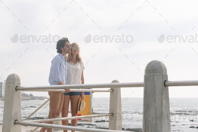 Side view of young Caucasian couple interacting with each other on the promenade at the seaside