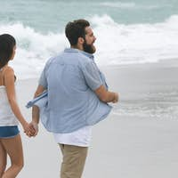 Rear view of caucasian couple walking on beach with hand in hand