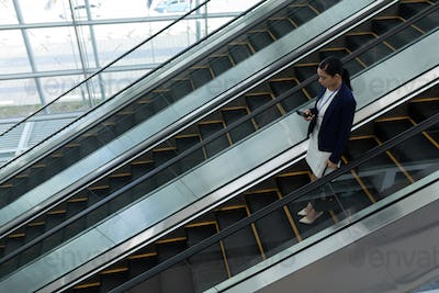 Mixed-race businesswoman using mobile phone while moving down on escalator in office
