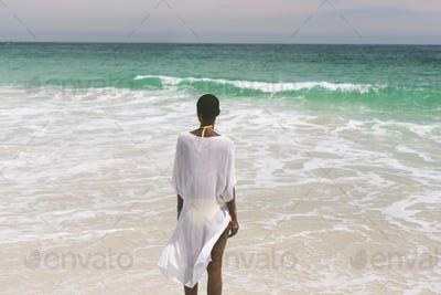 Rear view of African-american woman relaxing and standing looking at horizon on beach on a sunny day