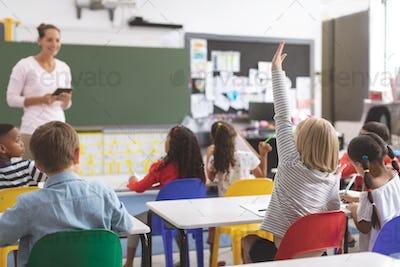Schoolgirl raising hand in classroom in front of her teacher
