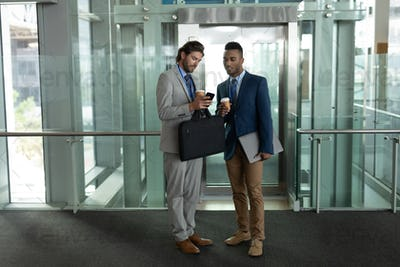 Young businessmen discussing over mobile phone near elevator in office