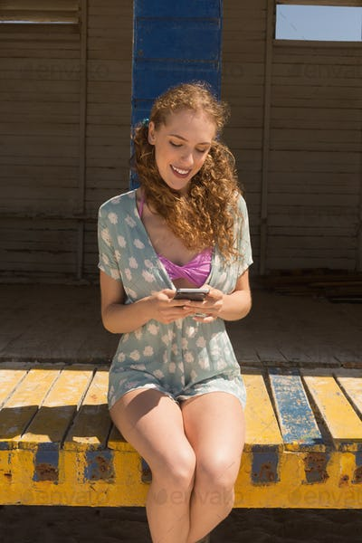 Front view of happy gorgeous young woman using mobile phone sitting on beach hut. She is smiling