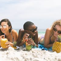 front view of happy multi ethnic women lying at beach while having pineapple juice on a sunny day