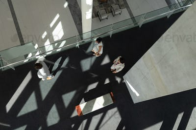 High angle view of business people arriving and walking at office lobby with ceiling shadows