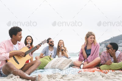 Front view of man playing guitar while friends enjoying on beach while having beer