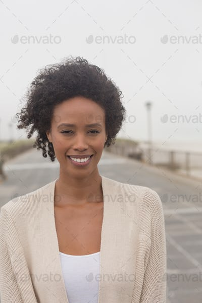 Portrait of happy young African American woman looking at camera on promenade. She is smiling