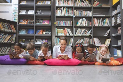 Schoolteacher lying with his school kids  and using digital tablet in a library at school