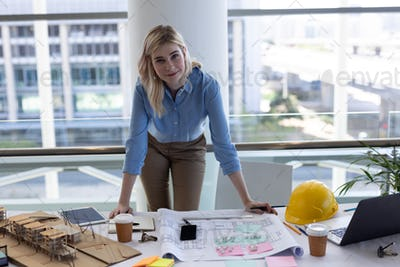 Blonde female architect looking at camera at desk in modern office