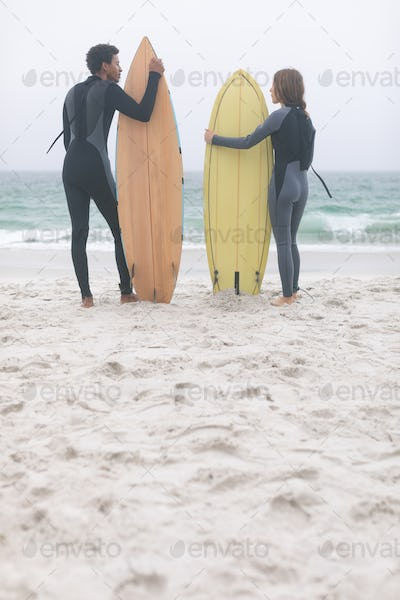 Rear view of young multi-ethnic couple surfer holding surfboards on the beach