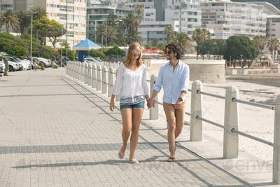 Young couple walking hand in hand on the promenade at the seaside on sunny day
