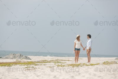 Front view of young Caucasian couople standing at beach n a sunny day