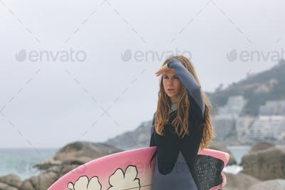 Front view of caucasian woman standing with surfboard shielding eyes at beach