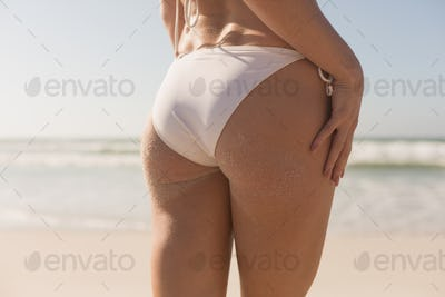 Mid section of young Caucasian woman in bikini standing on the beach. It is sunny day