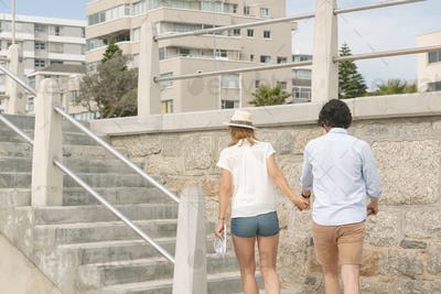Rear view of young Caucasian couple walking hand in hand near sea side at promenade on a sunny day