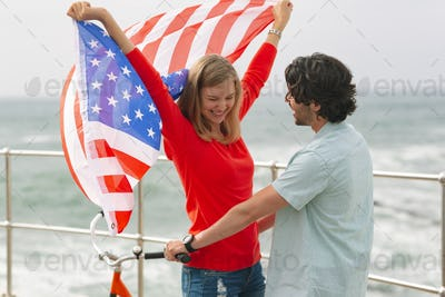 Romantic young couple standing at promenade while holding american flag
